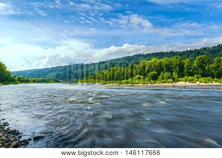 Beautiful river landscape with cloudy blue sky reflected in the clear water. Wooded waterside of a mountain lake. Summer idyllic landscape.