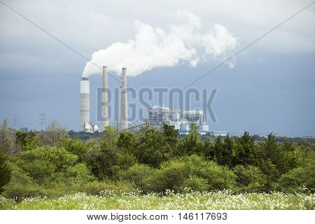Steam rises from a refinery plant across an open field.