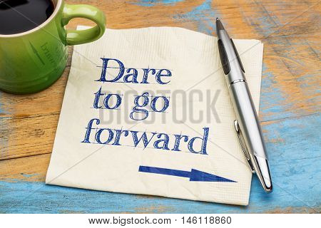 Dare to go forward - handwriting on a napkin with a cup of espresso coffee