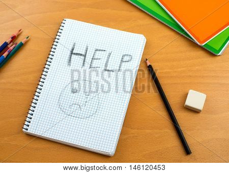A Horizontal image /poster covering the Social Issues of child abuse a note left on a desk by a child asking for help by a written message saying Help with a sad face . Room for copy space and text