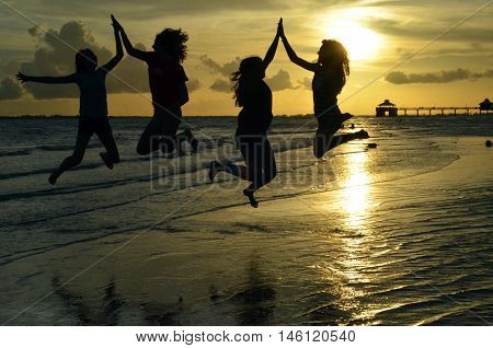 Four girls jumping and giving high-fives in front of a sunset