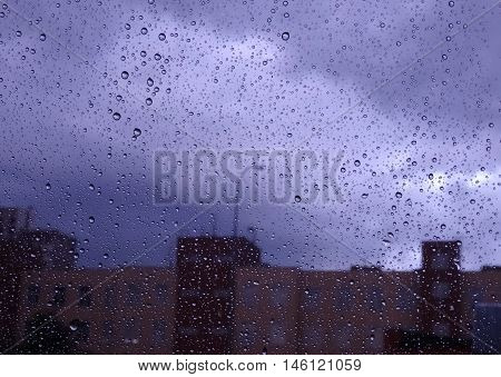 Look on rain at city through wet window glass stock photo