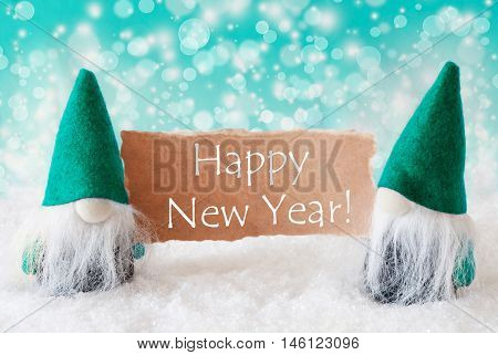 Christmas Greeting Card With Two Turqoise Gnomes. Sparkling Bokeh Background With Snow. English Text Happy New Year