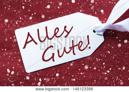 One White Label On A Red Textured Background. Tag With Ribbon And Snowflakes. German Text Alles Gute Means Best Wishes