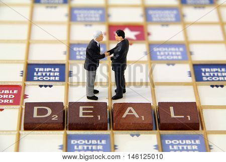 Two business men figurines closing a business deall.
