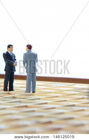 Two business men on a game board having a conversation.