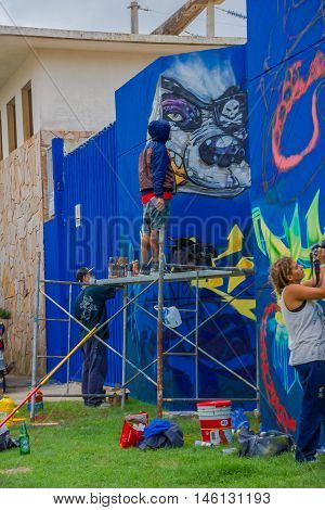 PUNTA DEL ESTE, URUGUAY - MAY 06, 2016: unidentified young men painting some grafittis on the wall.