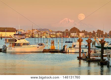 the moon rising over steveston harbor next to mount baker. british columbia, canada.