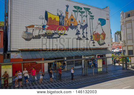 CURITIBA , BRAZIL - MAY 12, 2016: unidentified people waiting for the bus in a station under a painted wall.