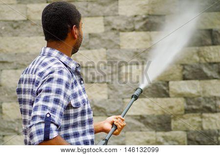 Man wearing square pattern blue and white shirt holding high pressure water gun, pointing towards grey brick wall.