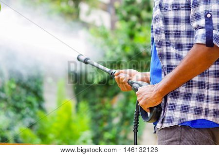 Closeup arms of man wearing square pattern blue and white shirt holding high pressure water gun, pointing towards green garden.