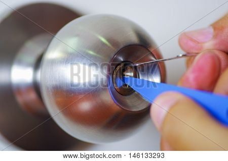 Closeup hands of locksmith using pick tools to open locked door.