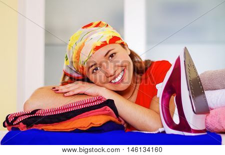 Young charming woman wearing colorful headscarf resting head on stack of clothes, ironing laundry housework concept.