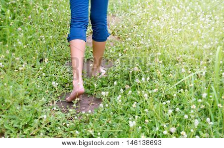 Bare feet of a kid walking on rock garden in the rainy season, through a green field and flower of grass, copy space, back to nature, back to nature