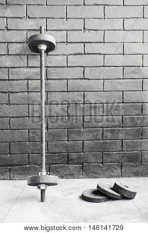 Iron metal barbell dumbbell bar against brick wall background
