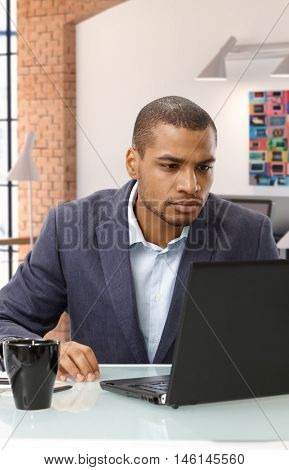 Busy, serious afro american business office desk worker with laptop computer. Sitting at table, looking at screen. Suit no tie.