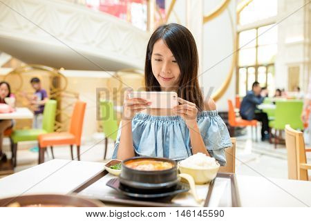 Woman taking photo on mobile phone before having the meal