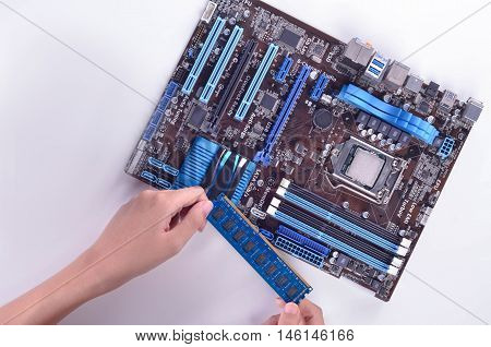 computer motherboard isolated in whitebackground with a person hand placing an equipment into the motherboard