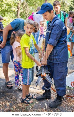 Zaporizhia/Ukraine- September  3, 2016: Charity festival for children - City of professions . Rescue service volunteer demonstrates hydraulic rescue equipment - spreader to  teen boy.