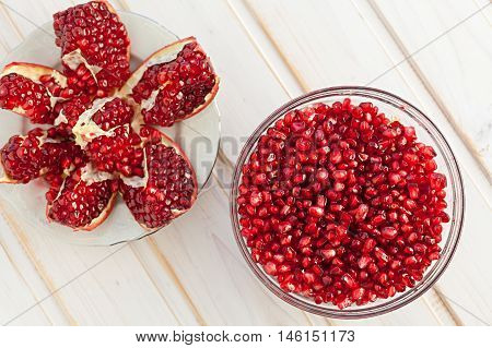 juicy pomegranate seeds in a glass bowl and lobules, top view