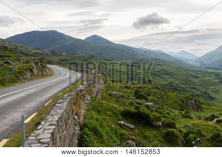 travel, trip and countryside concept - view to asphalt road and rocky hills at connemara in ireland