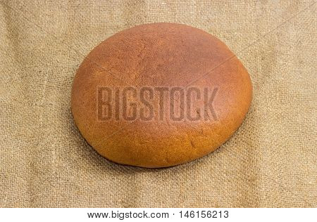 Whole round loaf of wheat and rye hearth bread on a sackcloth