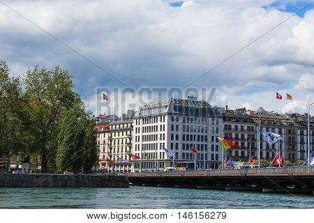 Geneva, Switzerland - June 17, 2016: Lake Geneva Embankment, bridge with flags. The Lake Geneva is a lake on the north side of the Alps, shared between Switzerland and France.