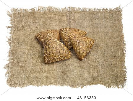 Several small multigrain triangular shaped bread sprinkled with whole sunflower seeds flax and sesame seeds on a sackcloth on a light background
