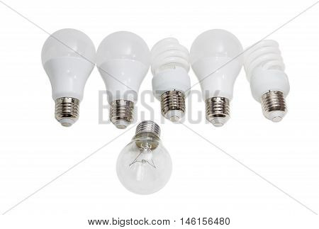 Incandescent lamp against several modern energy saving electric lamps - compact fluorescent lamps and light emitting diode lamps on a light background