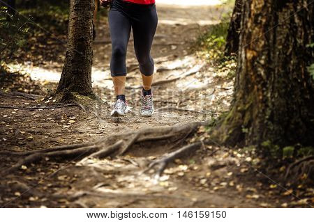 woman runs in woods trail land roots of trees legs grey capri tights leggings