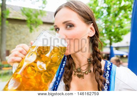 Woman wearing Dirndl is drinking beer in a Bavarian beer garden