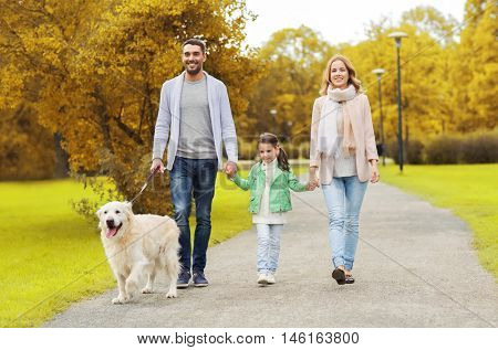 family, pet, domestic animal and people concept - happy family with labrador retriever dog walking in autumn city park