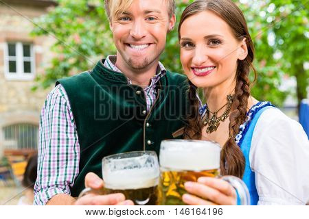 Couple, women and man, wearing Bavarian clothes is clinking beer glasses in a beer garden