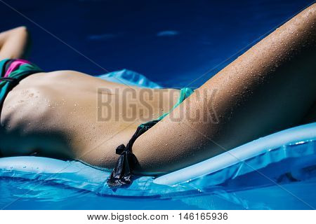 Female body of young woman with attractive tanned belly and legs in colorful bikini swimming and relaxing on air bed in summer pool with blue water