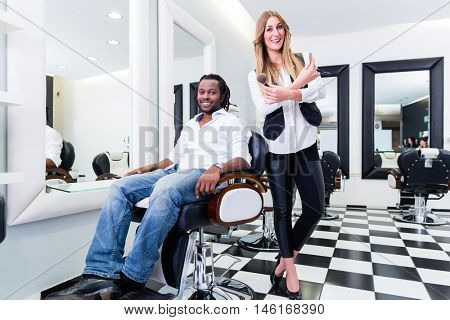 Barber und client in salon or shop, Caucasian professional and African customer