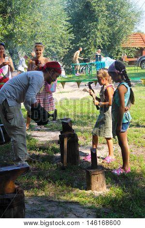 Myrgorod Ukraine - August 20 2016: Instructor teaches the girl blacksmithing on the festival of blacksmiths