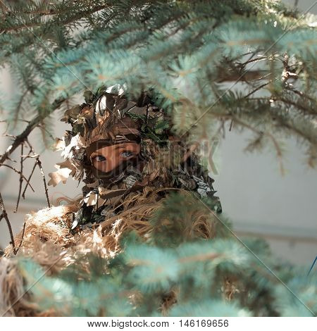 Young girl soldier defender with blue eyes face closed by mask in ghillie camouflage military ammunition with gun standing on background of spruce tree