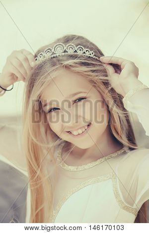 small girl kid with long blonde hair and pretty smiling happy face in dress and prom princess crown standing on white background closeup