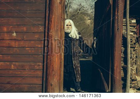 Druid old bearded man with long white hair and beard on serious face in fur coat sunny day outdoor on wood background