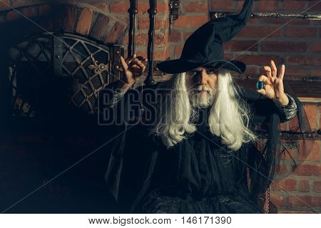 Old man wizard with long gray hair beard in black costume and hat for Halloween holding blue gem stone and silver pendant for hypnosis on wooden background