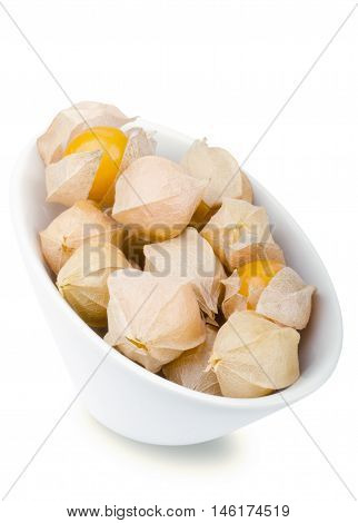 Physalis berries in white porcelain bowl over white. Edible ripe fruits of Physalis peruviana, a plant in the nightshade family. Light brown papery husks fully encloses the orange fruits. Macro photo.