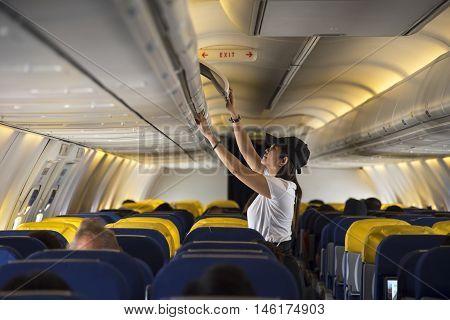 Traveller woman open overhead locker on airplane