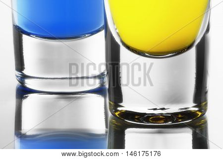 Blue and yellow cocktails in clean shot glasses. Downside of shot glasses with own reflection.