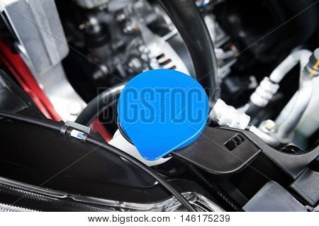 closeup blue windshield washer fluid reservoir cap in engine room