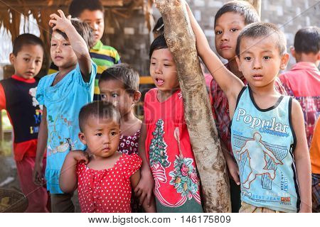 MANDALAY, MYANMAR - DECEMBER 2015: Small kids happily play together in a small village by Irrawaddy river of Bagan. These Burmese children are innocent, friendly, and welcoming. Bagan in Mandalay, Myanmar, is an ancient town and the most popular tourist d