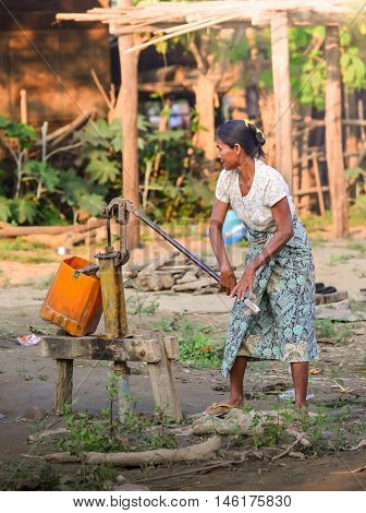 MANDALAY, MYANMAR - DECEMBER 2015: In evening light, a Bagan woman pumps water from a well in a village by Irrawaddy river of Baganm Mandalay, Myanmar.