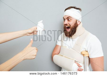 Freaky excited young bandaged man going to take medicine from container in doctors hand over gray background