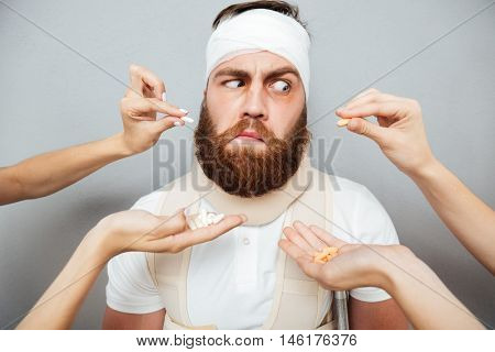 Mistrustful bandaged man hesitate about taking pills from doctors hands over gray background