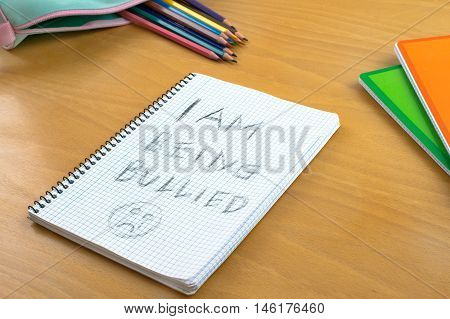 An Horizontal image / poster covering the Social Issues of child abuse a note left on a desk by a child asking for help by a written message saying I am being bullied with a sad face . Room for copy space and text