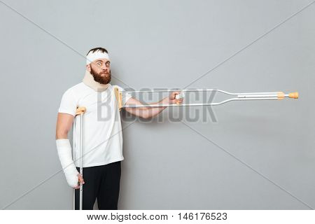 Funny bearded young man standing and pointing away with crutches over white background
